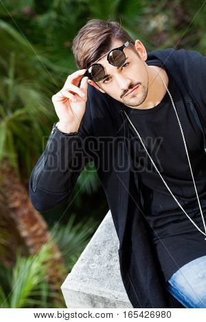 Young gorgeous man with sunglasses. Handsome man discovering his eyes moving up sunglasses. Chain around his neck. Outdoors.