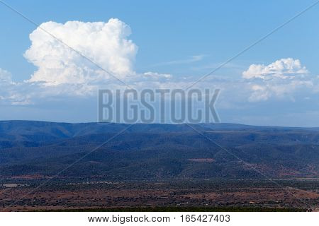 White Puffy Clouds Over The Dry Mountain Land