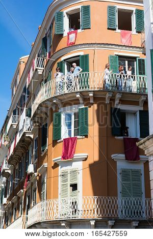 CORFU GREECE - APRIL 30, 2016: Buildings with red banners on balconies in anticipation of the Resurrection on the morning of Holy Saturday. Easter pot smashing.