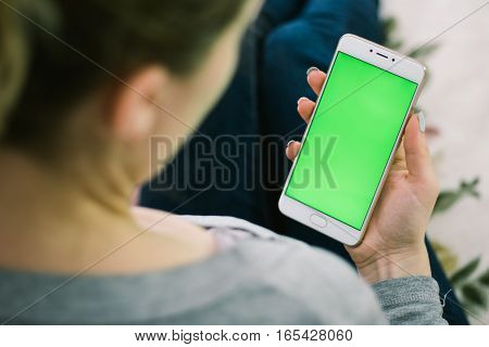 Beautiful girl holding a smartphone in the hands of a green screen green screen, hand of man holding mobile smart phone with chroma key green screen on white background, new technology concept