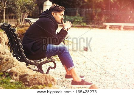 Thinking, thoughtful handsome man on the bench. Outdoors. Young and handsome man outdoors in a natural park. Light warm sunbeam.