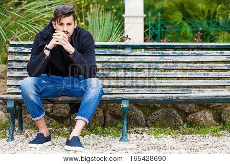 Handsome young man is sitting on a bench watching and waiting.