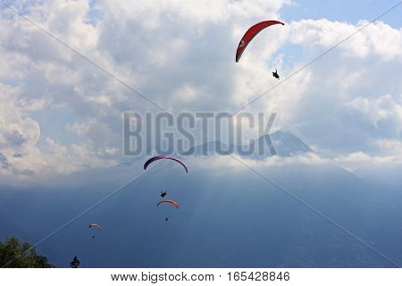 Paragliders under their wings in the French Alps