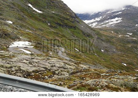 This is mountain road with a lot of serpentine that leads to Mount Dalsnibba Norway in severe weather.