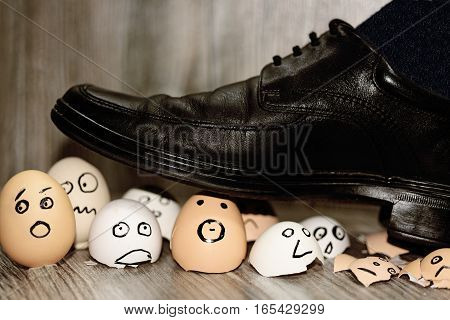 Abstract composition of business leadership. Broken eggs under mans shoes.