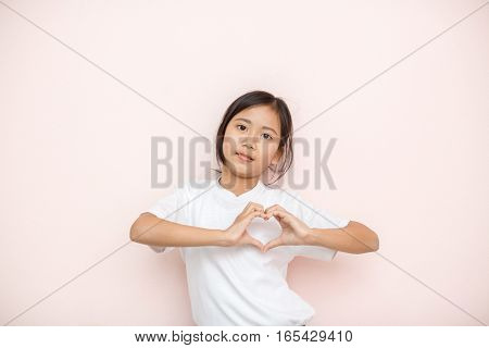Asian Tanned Skin Girl Child Portrait Over Pink Wall Background, Valentine Day Concept.