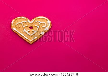 Cookies in shape of heart for Valentine's Day on on background of pink matte plastic. Festive treat for celebrating lovers. Holiday gingerbread with icing on polymer texture