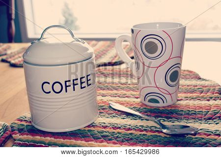 Close up of coffee mug with circle designs, spoon and tin coffee canister with lid and handle displayed on colorful place mat on wooden table.   Window in background. Instagram effects.
