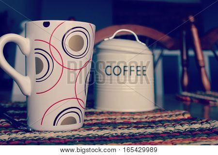 Close up of coffee mug with circle designs, spoon and tin coffee canister with lid and handle displayed on colorful place mat on wooden table.   Instagram effects.