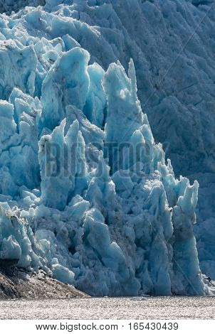 Blackstone Glacier pushes blue ice towards the ocean crumbling it into small pieces.