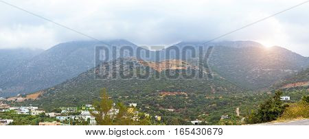 Mountainous nature of resort village Bali on island Crete in Greece. Low dark clouds hide tops of mountains morning cool and fog on hilly plateau. Rethymno Crete Greece