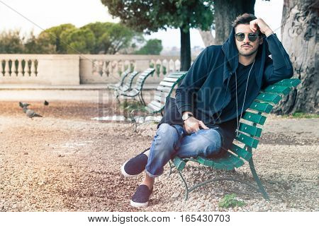 Fashionable cool young man with sunglasses relaxing on a bench. Outdoors in a park.