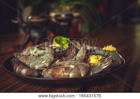 Savory marinated prawns for barbecue on black plate on wooden table during seafood cooking