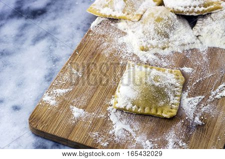 Floured italian ravioli with black pepper on a marble background