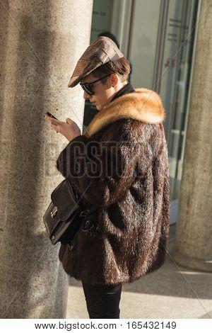 MILAN ITALY - JANUARY 14: Fashionable woman poses outside Antonio Marras fashion show building during Milan Men's Fashion Week on JANUARY 14 2017 in Milan.
