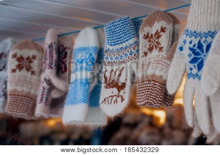 A variety of woolen mittens hanging on a rope