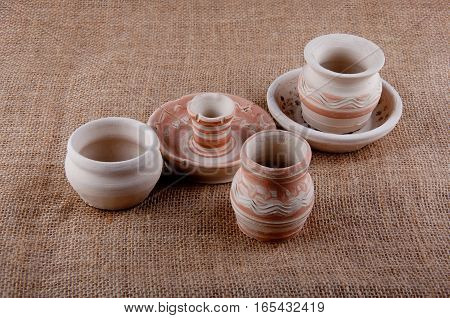 Ceramic goods. Three greybeards dish and candlestick with patterns on brown sackcloth background