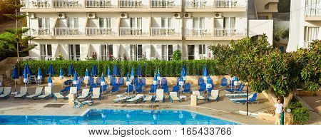 Bali Greece - April 29 2016: Relax and sunbathe by pool with clear blue water in Resort hotel Atali Village 4 star. Empty pool without tourists early morning at hotel. Bali Rethymno Crete Greece