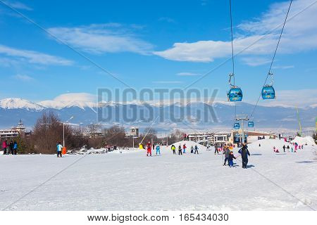 Bansko, Bulgaria - January 13, 2017: Winter ski resort Bansko, ski slope, people skiing and mountains view