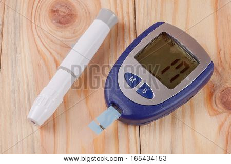 The blood glucose meter on a light wooden background.