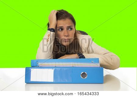 young attractive sad and desperate businesswoman suffering stress and headache at office desk looking worried depressed and overwhelmed with paperwork in green chroma key screen