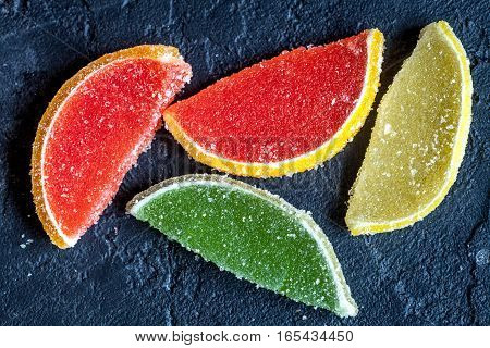 sweets and sugar candies on dark background top view.