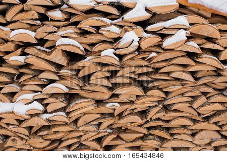 stack of firewood in winter snow in the village. open air. street
