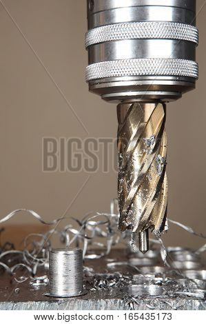 Close-up drilling machine making hole with annular cutter core drill.