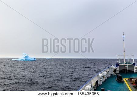 Ship bow and Iceberg drifting at Lemaire Channel Antarctica