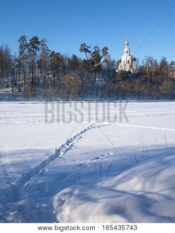 Landscape with frozen river and white Russian country church with golden cupola on hill over blue sky in winter