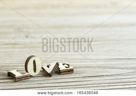 Close-up word love from carved wooden letters on the boards. broken love