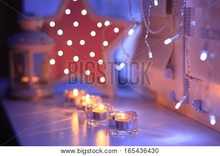 Celebration decoration for valentine day. Shiny candles in the evening. Blurred lights on backdrop. Candles on windowsill.