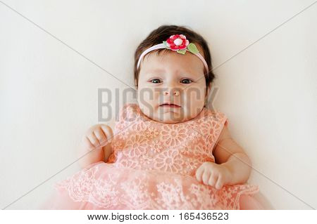 sweet newborn baby girl in a pink dress and a flower on the head with a sad face lies on a white blanket