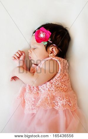 New born baby girl dressed in pink asleep on a white blanket