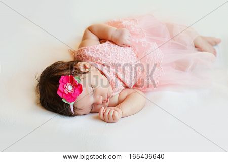 Newborn girl lying happy and relaxed on a blanket of white hair and dressed in pink