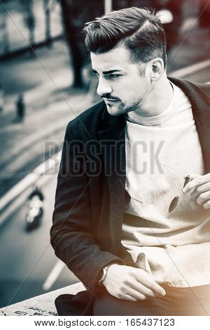 Handsome young man outdoors. Black and white. Sunglasses in hand and stylish hair. Behind him a city street.