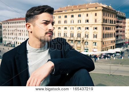 City handsome man, fashion modern hair. Handsome boy looking, stylish hair and modern clothes. Horizontal portrait behind him some historic buildings in Rome, Italy. Urban scene.