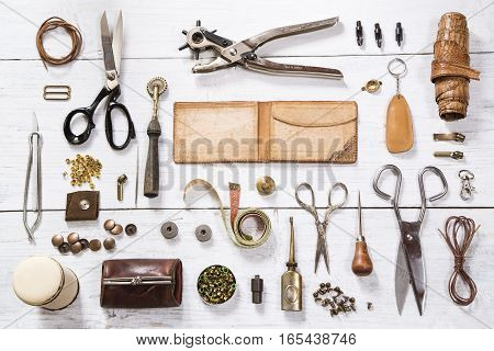 Leather craft tools on white wooden background