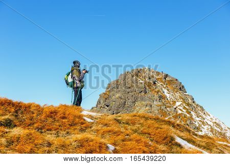 Woman taking photo, Tatra Mountains, Poland, autumn mountain landscape