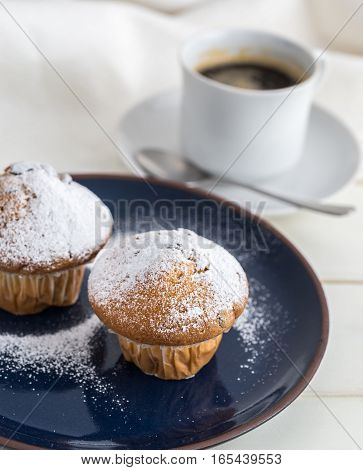 Breakfast with muffins by powdered sugar and coffee.