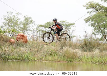 Young Boy Riding On Edge Of Dam At Mountain Bike Race