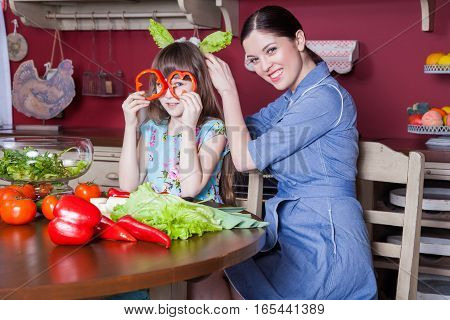 Happy mother and daughter enjoy making and having healthy meal together at their kitchen. they are making vegetable salad and having fun together. mom takes care of her daughter and teaches how to cook.