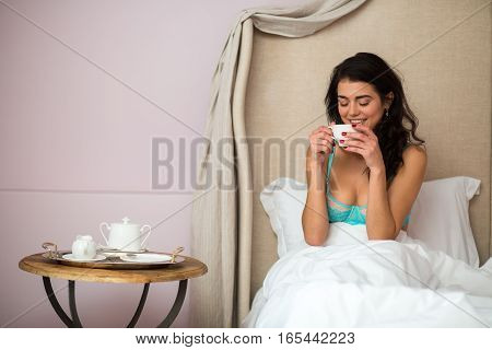 Woman in bed with cup. Young female indoor. My morning starts from coffee.
