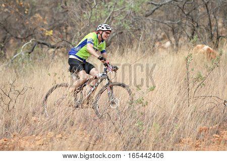 Aged Male Riding Through Bush At Mathaithai Mountain Bike Race