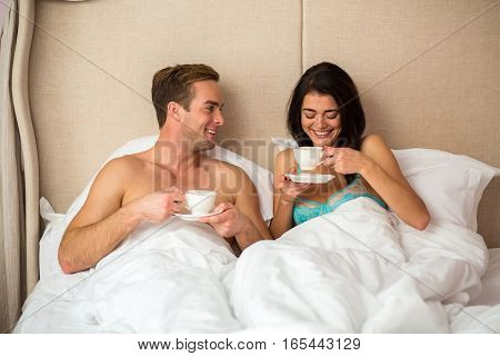 Couple in bed with cups. Smiling man and woman.Have a chat with beloved.