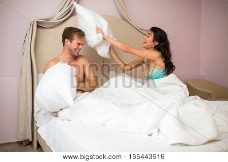 Couple is fighting by pillows. Young woman and man indoor. Fooling around like kids.