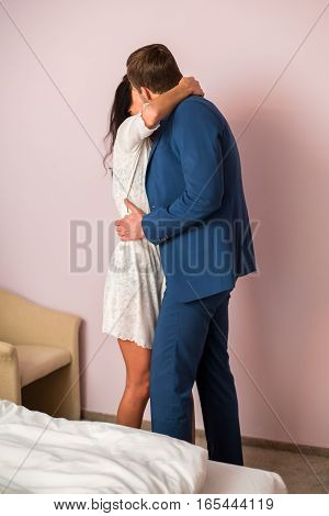 Man in suit kissing woman. Couple in a room. You are my drug.