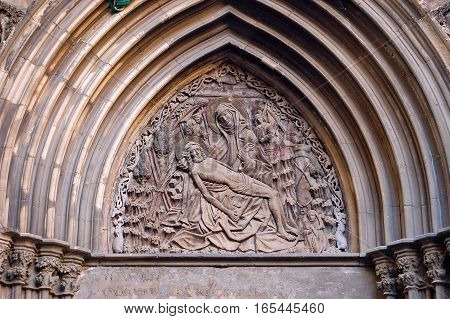 Pieta in the tympanum of the Cathedral of Barcelona in Catalonia, Spain