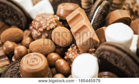 Mix of chocolate, candies, and cookies on table, close-up