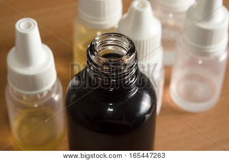 E cigarettes Liquid Bottle on wooden a table, close up